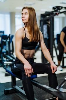 Vrij sexy geschiktheidsvrouw met perfect gespierd lichaam die op simulator bij gymnastiek rusten.