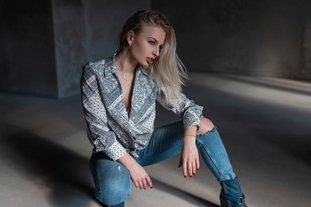 Vrij sexy mooie jonge vrouw model in een vintage shirt met een patroon in gescheurde spijkerbroek in stijlvolle schoenen poseren in een grijze studio op een zonnige dag