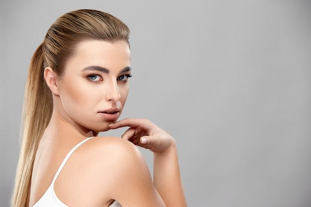 Vrij sexy vrouw raakt haar kin, kopie ruimte, profiel shot van blond meisje met naakt make-up