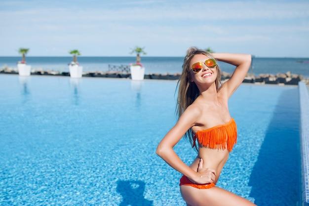 Vrij slank blond meisje staat in de buurt van het zwembad op de zon. ze poseert en lacht naar de camera.
