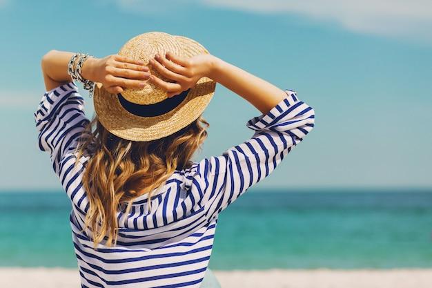 Vrij slanke bruine blonde stijlvolle vrouw in strooien hoed en zonnebril, die zich voordeed op het paradijs tropische strand