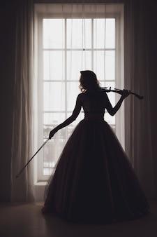 Vrij slanke jonge vrouw met viool bij raam