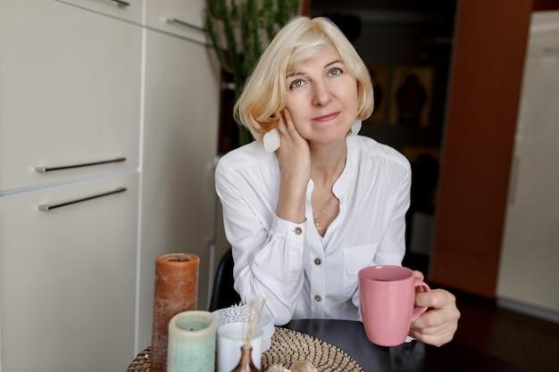 Vrij slanke rijpe blonde vrouw die van ochtend met koffie geniet