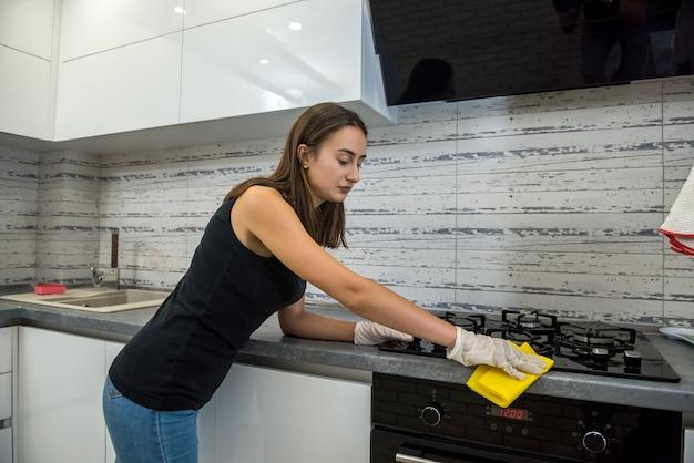 Vrij slanke vrouw in beschermende handschoenen met een vod algemene reiniging in de keuken. huiswerk