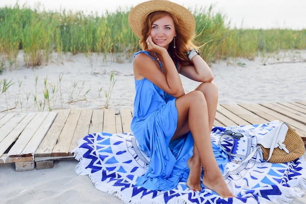 Vrij slanke vrouw met lange rode haren in strohoed geweldige vakantietijd doorbrengen op het strand. blauwe jurk dragen. zittend op een stijlvolle hoes.