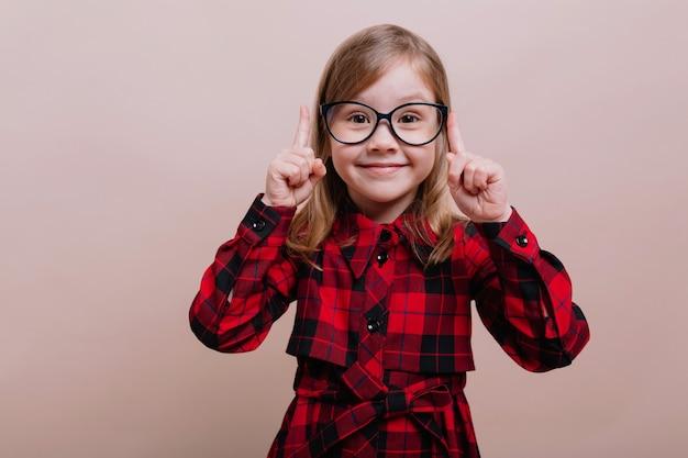Vrij slim meisje dat zich over beige muur bevindt die grote finfer tegenhoudt en camera met glimlach bekijkt