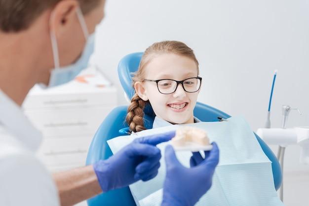 Vrij slim nieuwsgierig meisje kijkt naar het model dat haar arts vasthoudt terwijl ze enkele dingen over mondhygiëne uitlegt