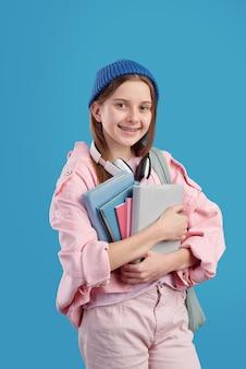 Vrij slim tienermeisje met boeken door borst die zich voor camera tegen blauwe achtergrond bevinden en u met glimlach bekijken
