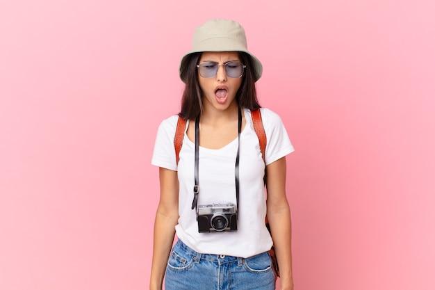 Vrij spaanse toerist die agressief schreeuwt, erg boos kijkt met een fotocamera en een hoed
