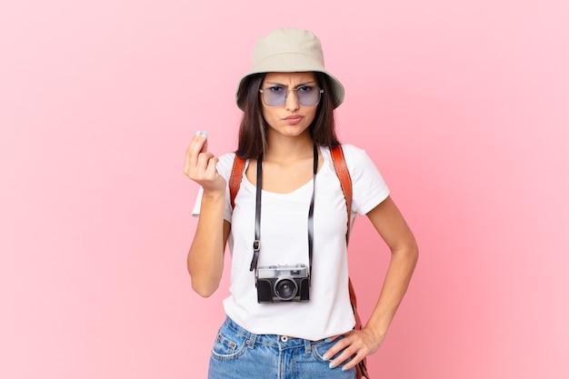 Vrij spaanse toerist die capice of geldgebaar maakt en zegt dat je moet betalen met een fotocamera en een hoed