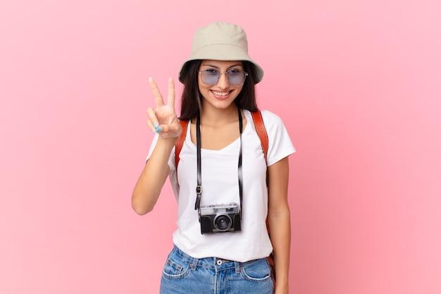 Vrij spaanse toerist die lacht en er gelukkig uitziet, gebarend naar overwinning of vrede met een fotocamera en een hoed
