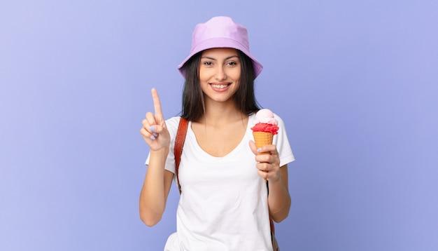 Vrij spaanse toerist die lacht en er vriendelijk uitziet, nummer één laat zien en een ijsje vasthoudt
