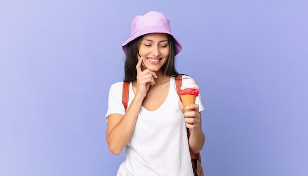 Vrij spaanse toerist die lacht met een vrolijke, zelfverzekerde uitdrukking met de hand op de kin en een ijsje vasthoudt
