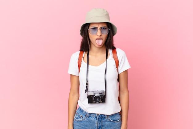 Vrij spaanse toerist die walgt en geïrriteerd voelt en zijn tong uitsteekt met een fotocamera en een hoed
