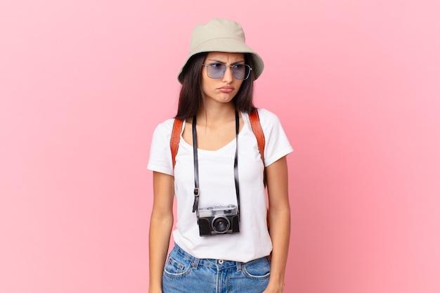 Vrij spaanse toerist die zich verdrietig, overstuur of boos voelt en opzij kijkt met een fotocamera en een hoed