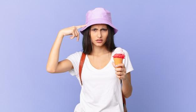 Vrij spaanse toerist die zich verward en verbaasd voelt, laat zien dat je gek bent en een ijsje vasthoudt