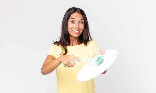 Vrij spaanse vrouw die een epty schone schotel houdt