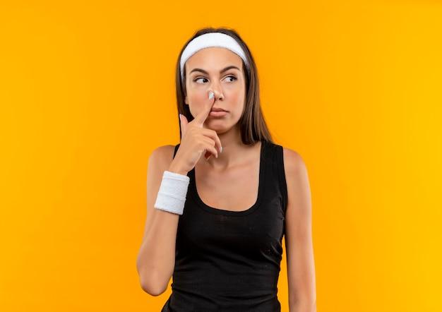 Vrij sportief meisje dat hoofdband en polsband draagt die vinger in neus aanbrengt en kant bekijkt