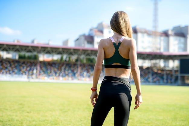 Vrij sportief meisje in het stadiongras gymnastiekoefeningen doen.