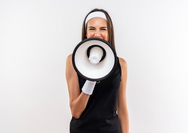 Vrij sportief meisje met hoofdband en polsband praten door spreker geïsoleerd op witte ruimte