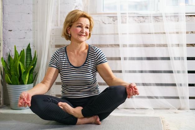 Vrij sportieve europese volwassen vrouw in sportkleding mediteert thuis in de kamer
