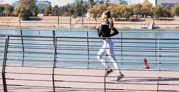 Vrij sportieve jonge vrouwenjogging bij park