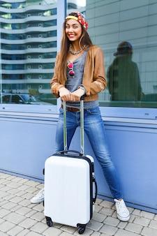 Vrij sportieve meisje poseren met haar bagage in de buurt van luchthaven