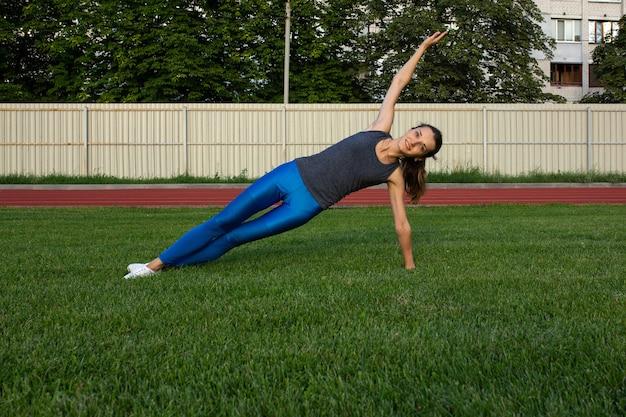 Vrij sportieve vrouw die zich uitstrekt voor de training op het gazon. ruimte voor tekst