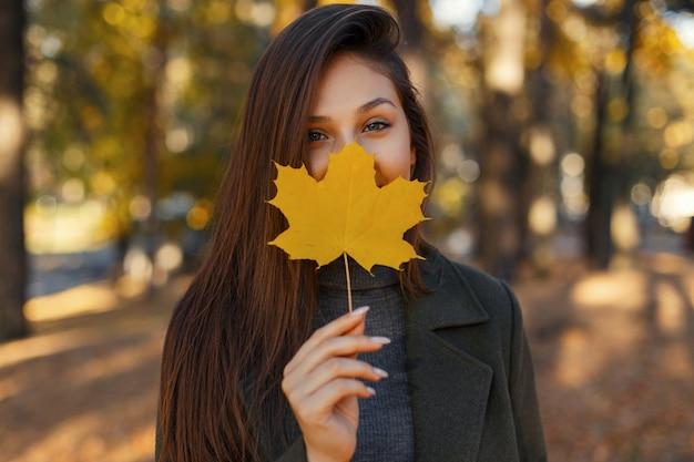 Vrij stijlvol meisje met blauwe ogen in een modieuze jas, met een geel herfstblad in de buurt van het gezicht tijdens een wandeling in het park. glimlachende vrouw.