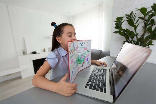 Vrij stijlvol schoolmeisje dat huiswerkwiskunde bestudeert tijdens haar online les thuis, sociale afstand tijdens quarantaine, zelfisolatie, online onderwijsconcept, thuisonderwijs