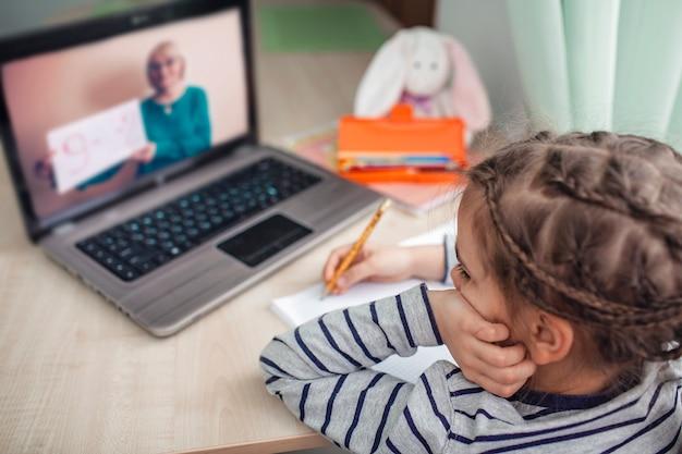 Vrij stijlvol schoolmeisje dat wiskunde bestudeert tijdens haar online les thuis, zelfisolatie