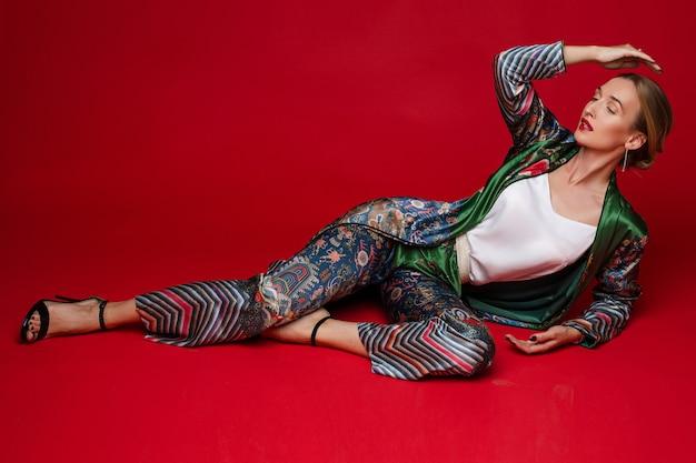 Vrij stijlvolle dame in een zijden pak poseren, geïsoleerd op rode muur