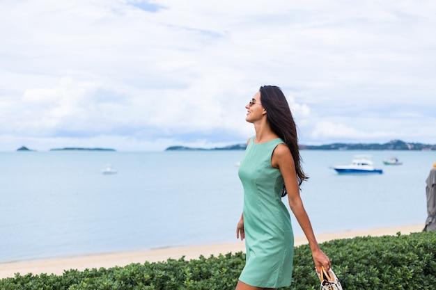 Vrij stijlvolle gelukkige vrouw in groene zomerjurk met tas, zonnebril dragen op vakantie, blauwe zee op achtergrond