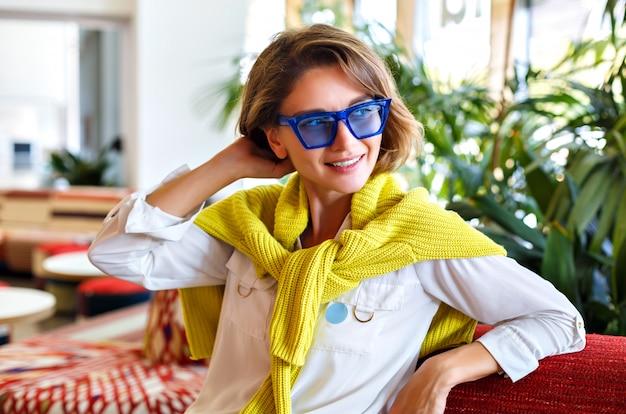 Vrij stijlvolle vrouw poseren in restaurant, palmbomen rond, zonnebril en gele neon trui, casual slimme look, natuurlijke make-up, korte haarstijl.