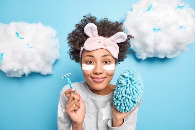 Vrij tevreden afro-amerikaanse vrouw glimlacht zachtjes ondergaat huidverzorgingsprocedures draagt slaappak schoonheidspatches onder de ogen om rimpels te verminderen houdt scheermesbad spons geïsoleerd op blauwe muur