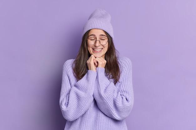 Vrij tevreden brunette vrouw houdt de handen onder de kin, sluit de ogen en voelt zich verrukt blij om iets goeds te horen gekleed in warme winter jumper muts grote bril.