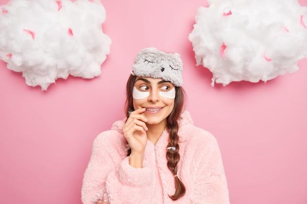 Vrij tevreden europees meisje glimlacht zachtjes heeft nieuwsgierige gezichtsuitdrukking geniet van comfort en serene sfeer thuis draagt slaapmasker met pyjama geïsoleerd over roze muur gaat slapen
