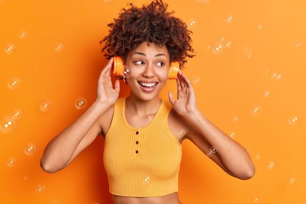 Vrij tevreden gekrulde harige vrouw draagt stereo koptelefoon op oren glimlacht in grote lijnen geniet van perfect geluid geconcentreerd weg gekleed in bijgesneden top geïsoleerd op oranje studio muur met vliegende zeepbellen