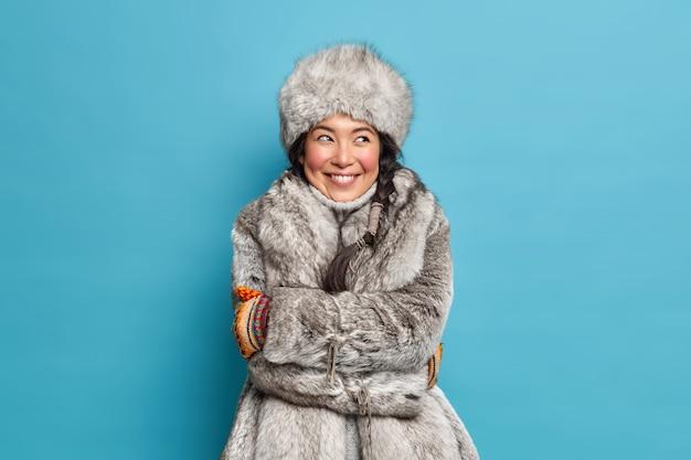 Vrij tevreden jonge eskimo-vrouw omhelst zichzelf voelt zich comfortabel in winterjas en hoed heeft dromerige uitdrukking geïsoleerd over blauwe muur
