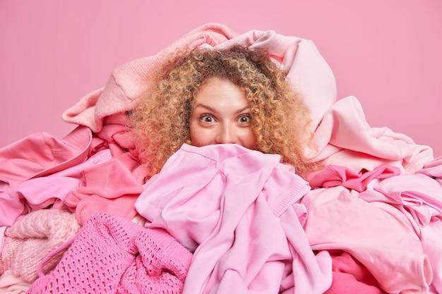 Vrij tevreden jonge vrouw met krullend haar bedekt met een grote hoop kleren verzamelt wasgoed om te wassen, doet de lenteschoonmaak in de kledingkast en bergt seizoenskleding en items op voor opslag.