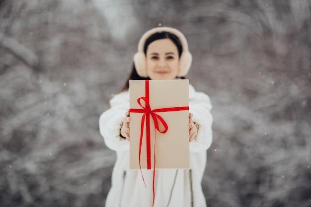 Vrij tienermeisje met een cadeau in haar handen voor valentijnsdag.