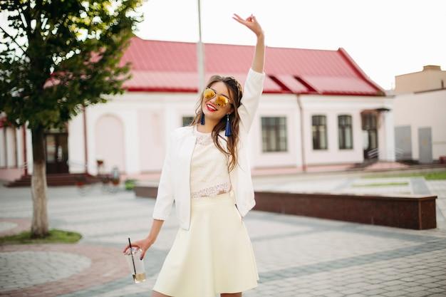 Vrij trendy meisje met vlecht in gespiegelde zonnebril koffie drinken in de straat.