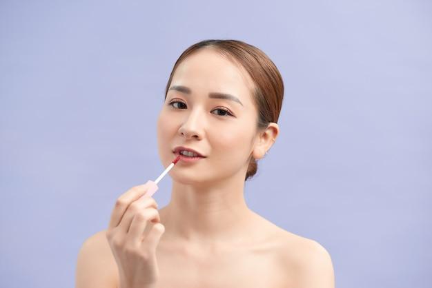 Vrij trendy stijlvol meisje test nieuwe lipgloss geïsoleerd op violet muur, perfectie, welzijn advertentie concept