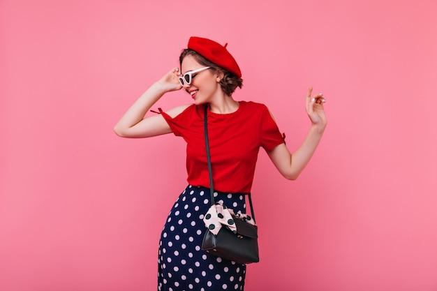 Vrij trendy vrouw in baret wat betreft haar zonnebril. indoor foto van vrolijk krullend brunette meisje in franse outfit.