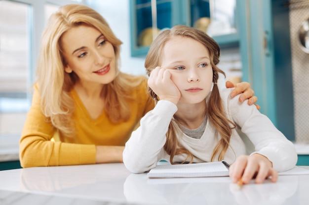 Vrij triest blond meisje zit aan de tafel met haar notitieboekje terwijl haar moeder achter haar zit en haar schouder aanraakt
