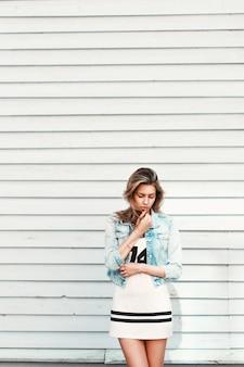 Vrij triest eenzaam meisje in de buurt van een witte houten muur
