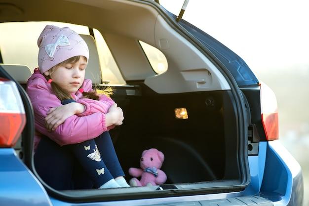 Vrij triest kind meisje zit alleen in een auto kofferbak met een roze speelgoed teddybeer.