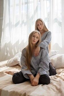 Vrij tweelingzusjes in jeans en gestreepte shirts met lange haren zittend op bed