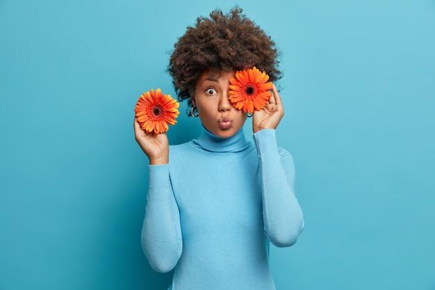 Vrij verbaasde vrouw bedekt ogen met oranje gerbera's, houdt bloemen vast, siert hal voor speciale gelegenheid, gekleed in blauwe coltrui, staat binnen.