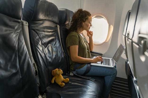 Vrij volwassen dame die naar het laptopscherm kijkt in het vliegtuig